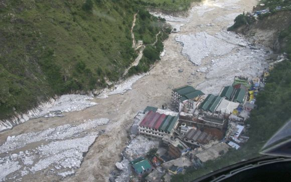 Flood waters flow next to a residential complex in Uttarakhand