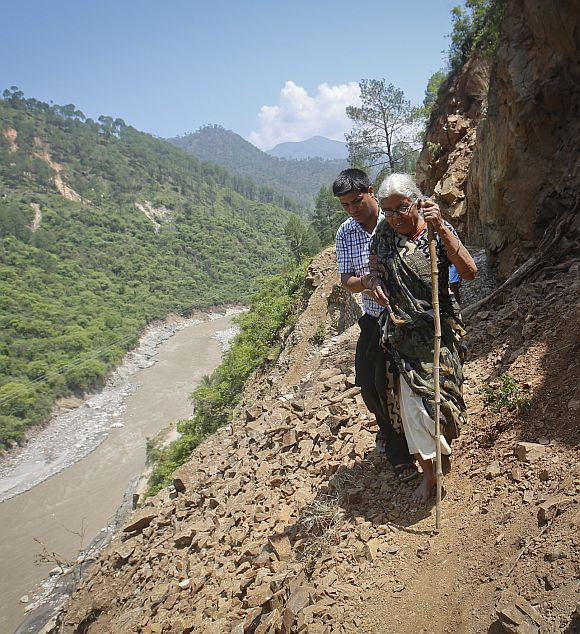 A pilgrim is helped by a villager as she tries to cross on a pathway damaged by landslide in Rudraprayag in the Himalayan state of Uttarakhand