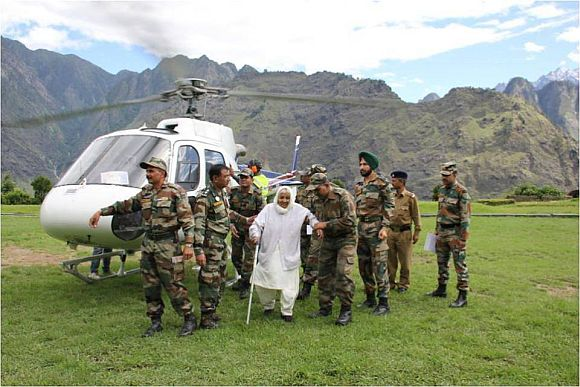 An elderly lady being escorted by Indian Army soldiers from a helicopter
