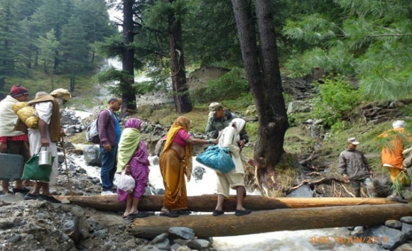 Army personnel evacuate people across a rivulet by laying a temporary bridge made of wooden logs on rout in Uttarakhand