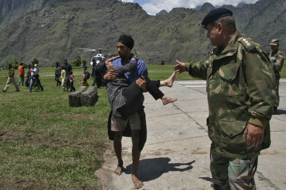 A man carries a flood affected victim after they were rescued by the Indian army in Uttarakhand