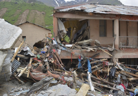 A body lies amid damaged surroundings by flood waters near Kedarnath Temple at Rudraprayag