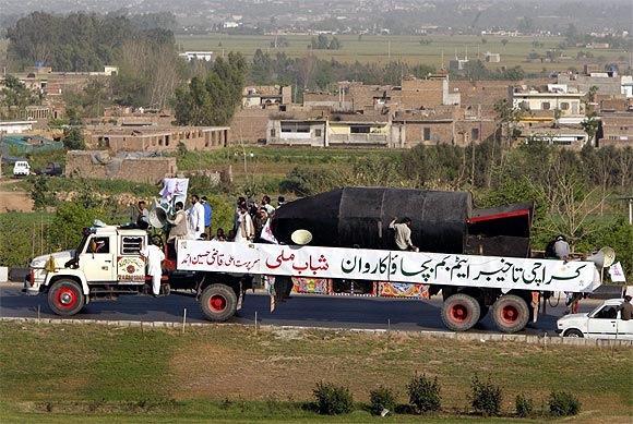 Members of the fundamentalist youth organisation Shabab-e-Milli drive a truck carrying a mock nuclear bomb through Islamabad