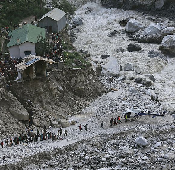 Soldiers assist survivors to board a rescue helicopter next to the River Alaknanda
