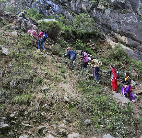 Pilgrims are helped to climb over a hill by Army soldiers during a rescue operation at Govindghat