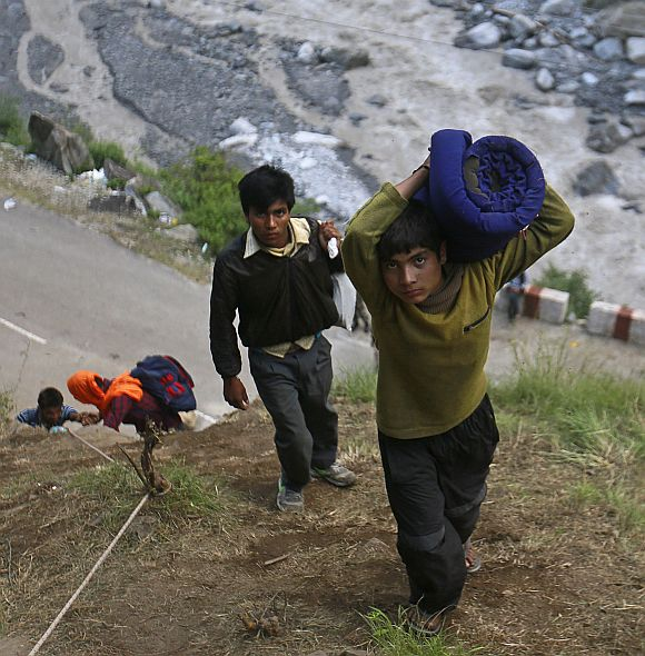 A boy carrying a bundle on his shoulder climbs over a hill during a rescue operation at Govindghat