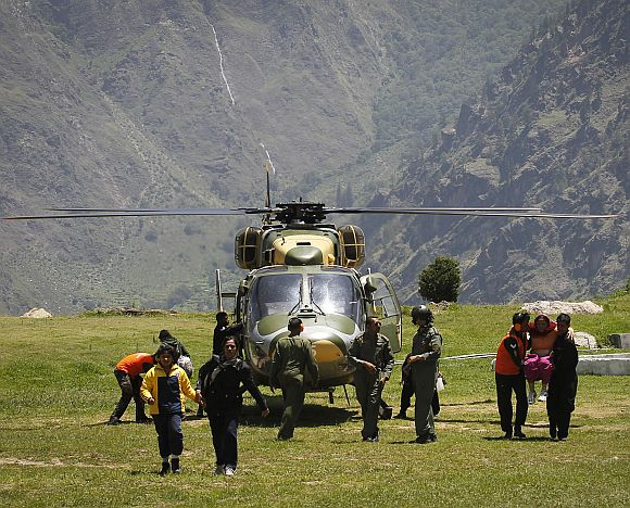 Survivors get out from an army helicopter during a rescue operation at Joshimath
