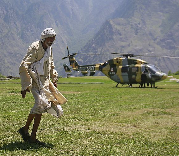 A man walks across a field after alighting from an army helicopter