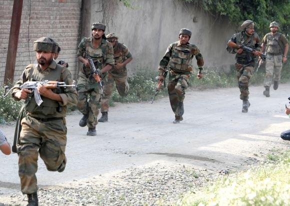 Army personnel taking positions after a militant strike on a convoy outside Srinagar on Monday