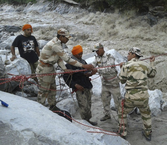 The Indo-Tibetan Border Police (ITBP) personnel rescue stranded people across a flooded river after heavy rains in the Himalayan state of Uttarakhand