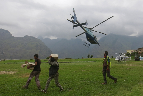 Soldiers carry boxes of relief supplies as an army helicopter flies overhead during a rescue operation at Joshimath