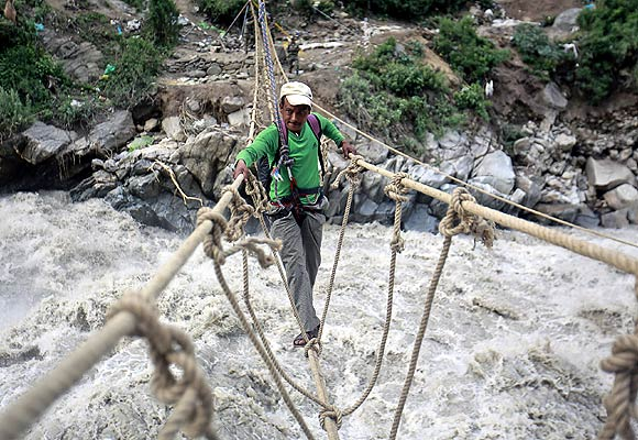 A man crosses a rope bridge over the Alaknanda river during rescue operations in Govindghat.