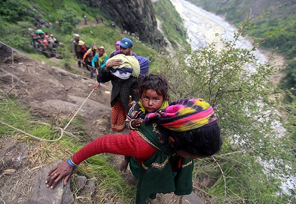 A woman carrying a child on her back climbs up a hill with other survivors during rescue operations in Govindghat.