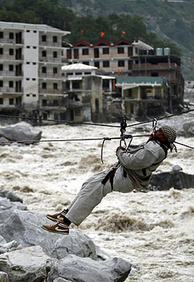 A man is pulled across to safety on a rope during a rescue operation in Govindghat on Sunday