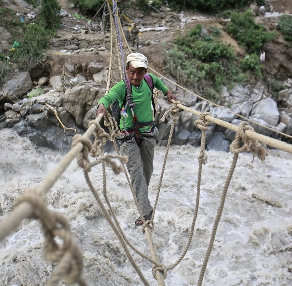 A man crosses a rope bridge over the Alaknanda river during rescue operations in Govindghat, Uttarakhand