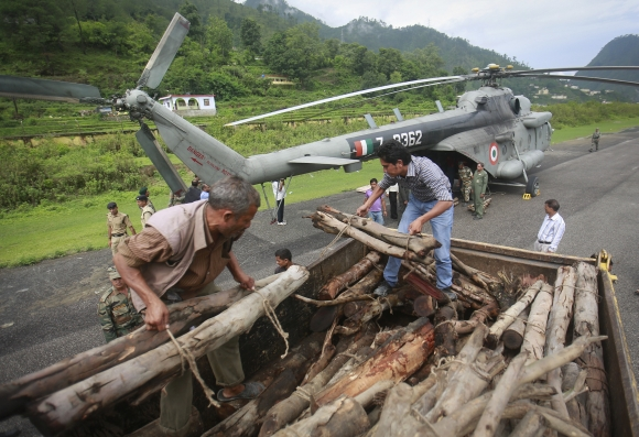 Volunteers unload wood from a truck to be used for mass cremation at Kedarnath at an airport in Gauchar