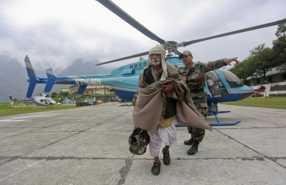 A man is guided by a soldier during a rescue operation at Joshimath