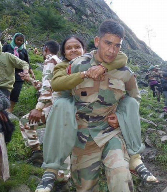 An Indian army personnel rescues a stranded pilgrim in Uttarakhand
