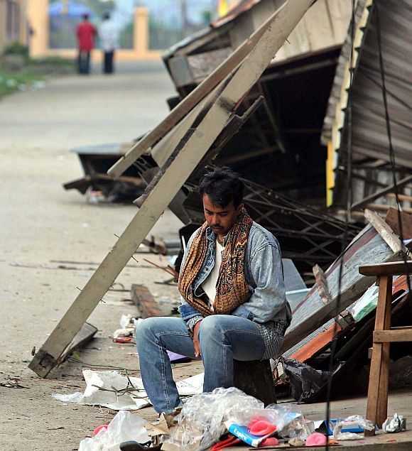 A man sits outside a damaged house after the massive earthquake