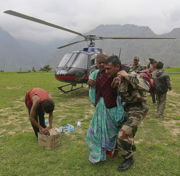 A woman is assisted by a soldier as she leaves an army helicopter during a rescue operation at Joshimath in the Himalayan state of Uttarakhand