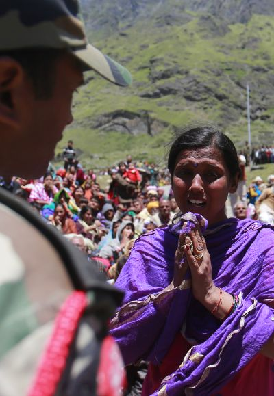 A survivor pleads with a soldier to allow her mother to board an army helicopter during rescue operations at flood-ravaged Badrinath, Uttarakhand.