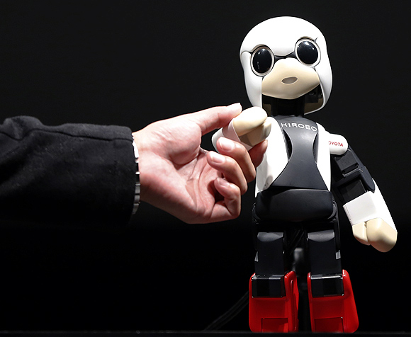 Kirobo shakes hands with Tomotaka Takahashi