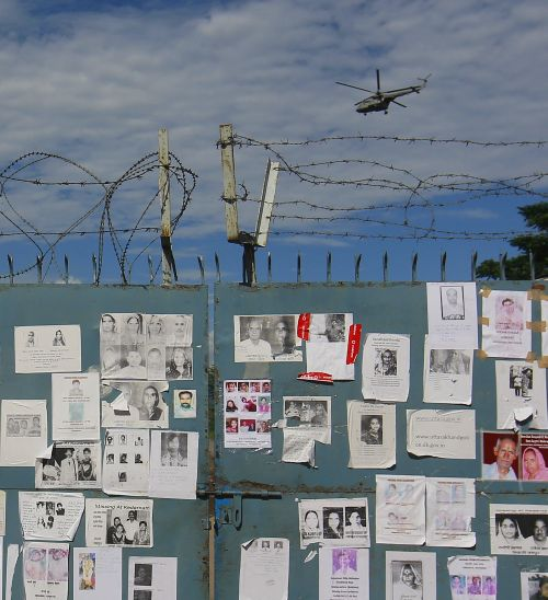 Posters of missing people, caused by the flash floods and landslides, are placed on a gate as an IAF helicopter lands at a base in Dehradun