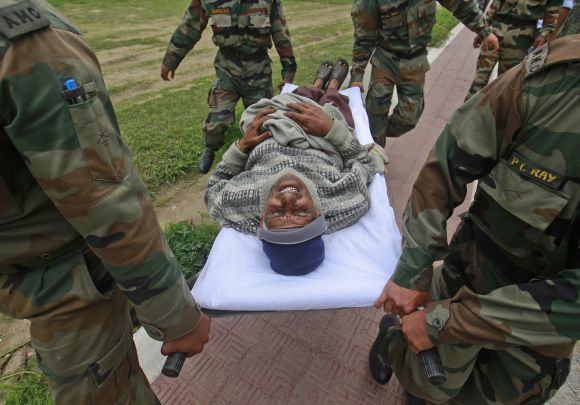An injured man is carried away by soldiers from an army helicopter during a rescue operation at Joshimath.