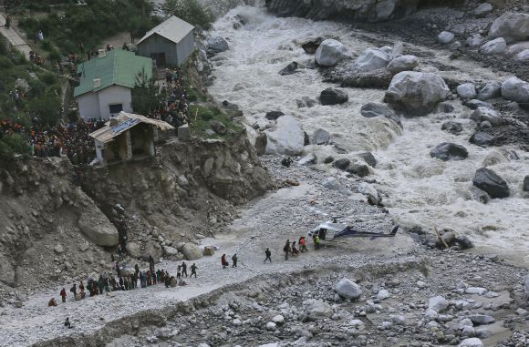 Soldiers assist survivors to board a rescue helicopter next to Alaknanda river, during rescue operations in Govindghat.