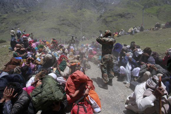 People and soldiers cover their faces as an army helicopter lands during rescue operations at Badrinath
