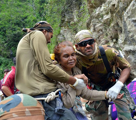 A frail woman being helped to safety In Uttarakhand