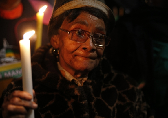 A woman holds a candle in support of ailing Mandela outside his former home in Soweto
