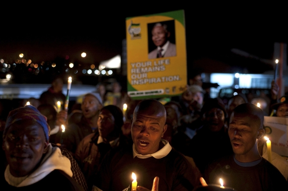Supporters hold candles as they gather in support of Mandela in Cape Town