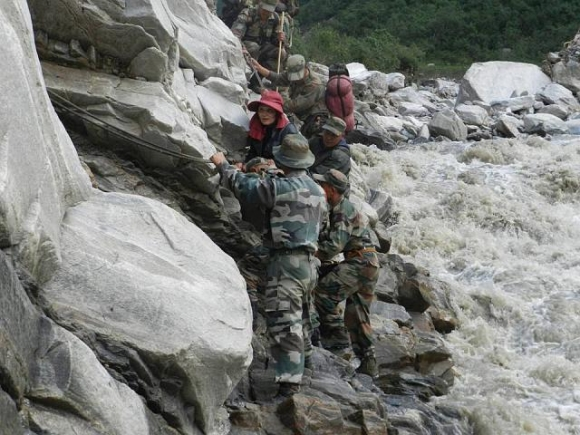 Army men help rescue a tourist who was stranded for weeks following the floods