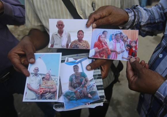 Relatives of missing people, affected by the flash floods and landslides, display their photographs outside the Indian Air Force base in Dehradun
