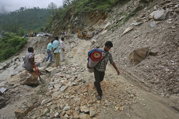 A villager crosses a road damaged by a landslide due to heavy rainfall in Gauchar