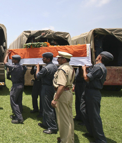 Soldiers load flag-draped coffins containing the bodies of rescue personnel who died in a chopper crash after a guard of honour ceremony in Dehradun