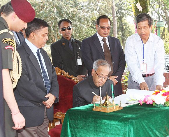 President Pranab writing a note in the visitor's book