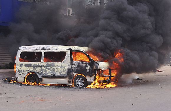 A minibus is set ablaze during a clash between Islamist activists and police in Dhaka