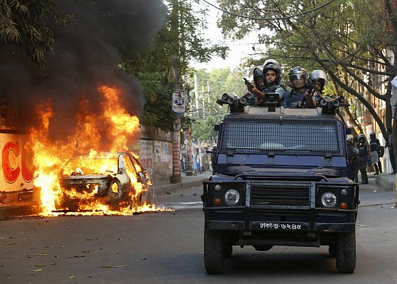 A police van passes a burnt vehicle after activists of Bangladesh Nation