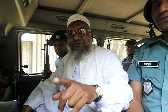 Bangladesh's Jamaat-e-Islami leader Abdul Quader Mollah gestures as he talks from a police van after the war crimes tribunal sentencing