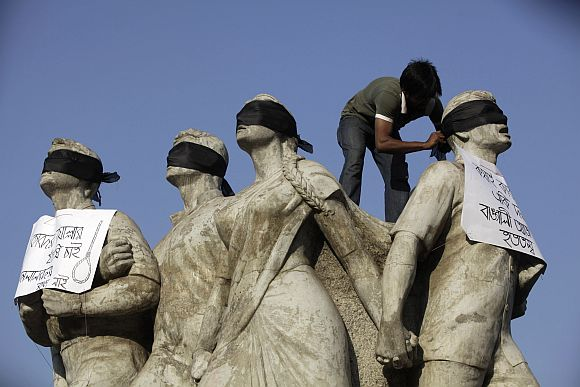 A student activist puts black scarves on the eyes of Shoparjito Shadhinota, a sculpture that represented all sections of people in Bangladesh's liberation War in 1971, demanding capital punishment for Bangladesh's Jamaat-e-Islami senior leader Abdul Quader Mollah