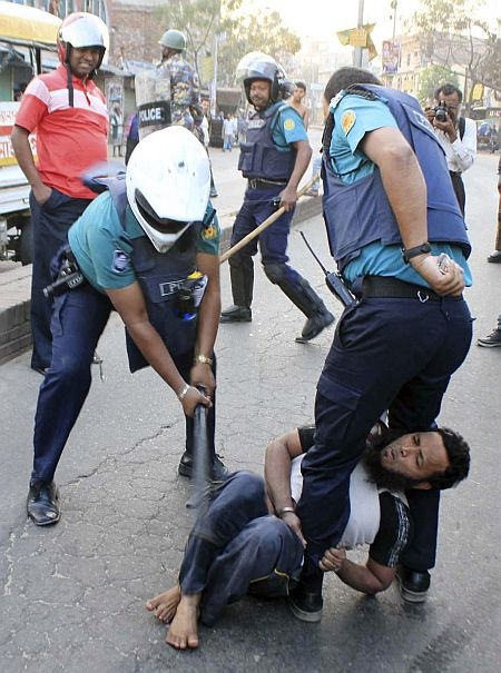 A policeman uses a baton on an activist of Jamaat-e-Islami, Bangladesh's biggest Islamist party, during a clash at Jatrabari in Dhaka