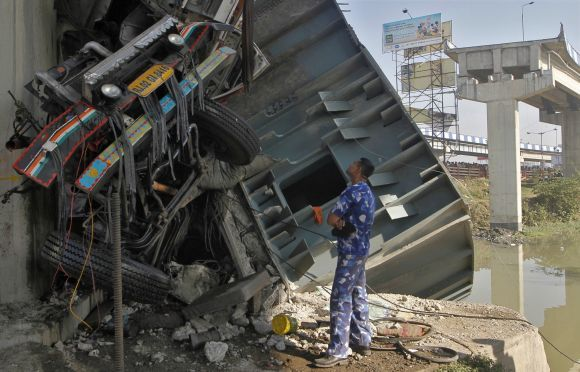 A rescue team member stands next to the wreckage of a damaged truck at the site of a collapsed flyover in Kolkata