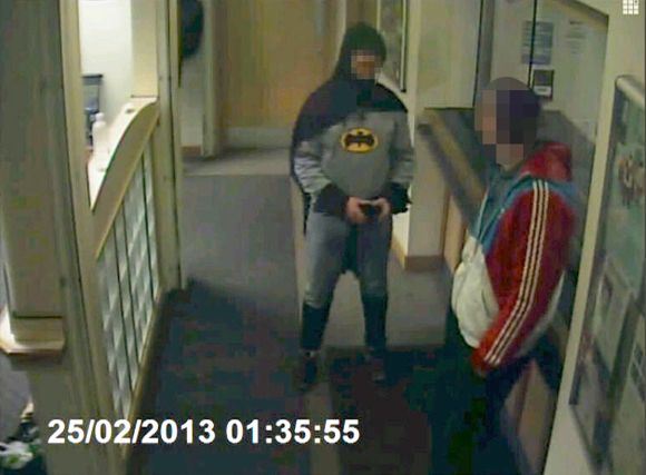 A man dressed as Batman and a burglary suspect stand in a police station in Bradford, northern England, on February 25, 2013, in this photograph taken from a CCTV video.