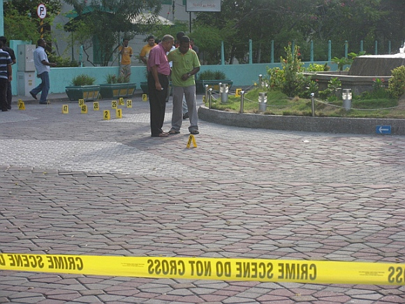 People stand near a mosque, where a blast occurred near the mosque at the entrance to the capital's Sultan Park, in this September 29, 2007 photograph