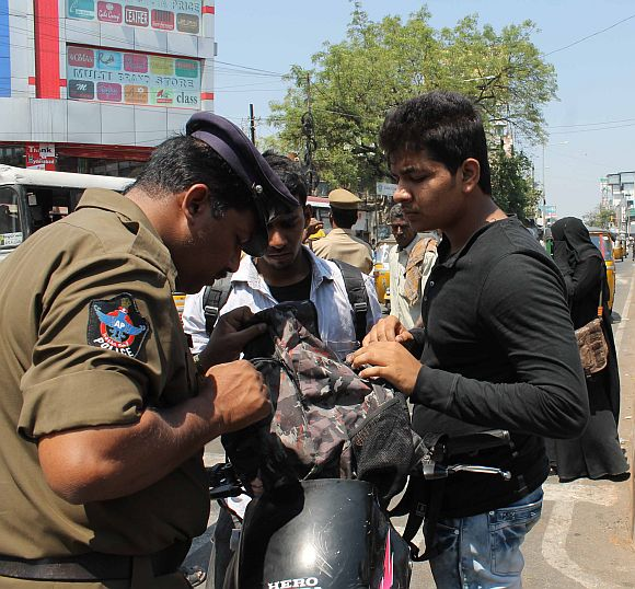 A policeman checks the bag of a biker in Hyderabad