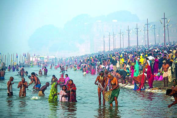 Devotees bathe in the waters of Sangam, the confluence of the holy rivers Ganga, Yamuna and the mythical Saraswati, during the Maha Kumbh Mela