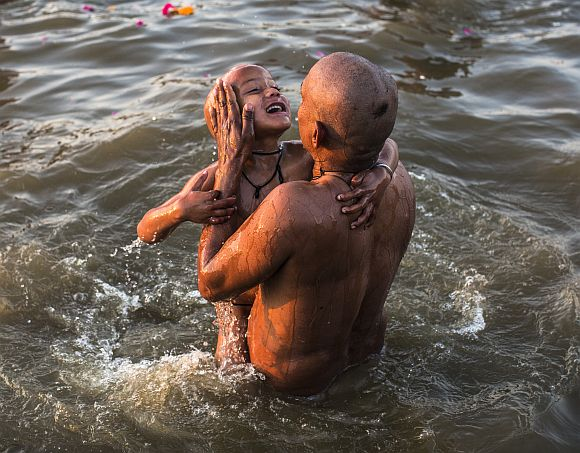A father dips his son into the waters of the Sangam during the Maha Kumbh Mela