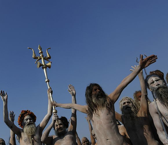 Sadhus gesture as one of them holds a trishul or trident-shaped weapon after taking a dip during the second Shahi Snan (grand bath), of the ongoing Kumbh Mela